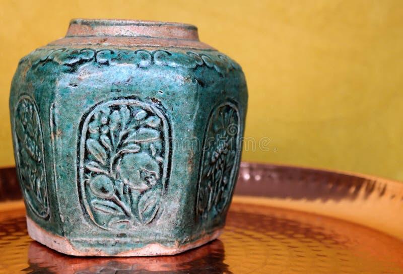 Barattolo dello zenzero del turchese su un vassoio d'ottone con un fondo ocraceo fotografia stock libera da diritti