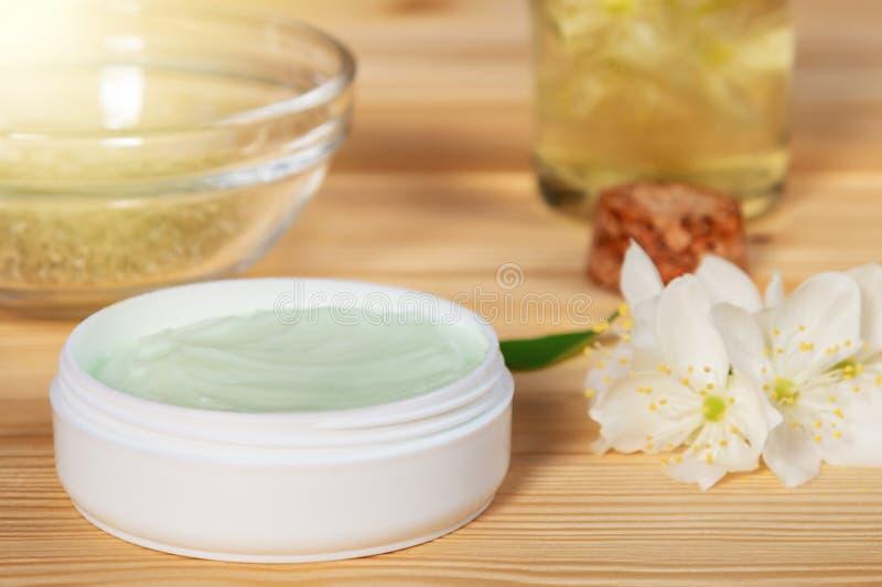 Barattolo di crema fatto dagli ingredienti della pianta, dai petroli e dalle erbe naturali, fiori del gelsomino su un fondo di le fotografia stock libera da diritti