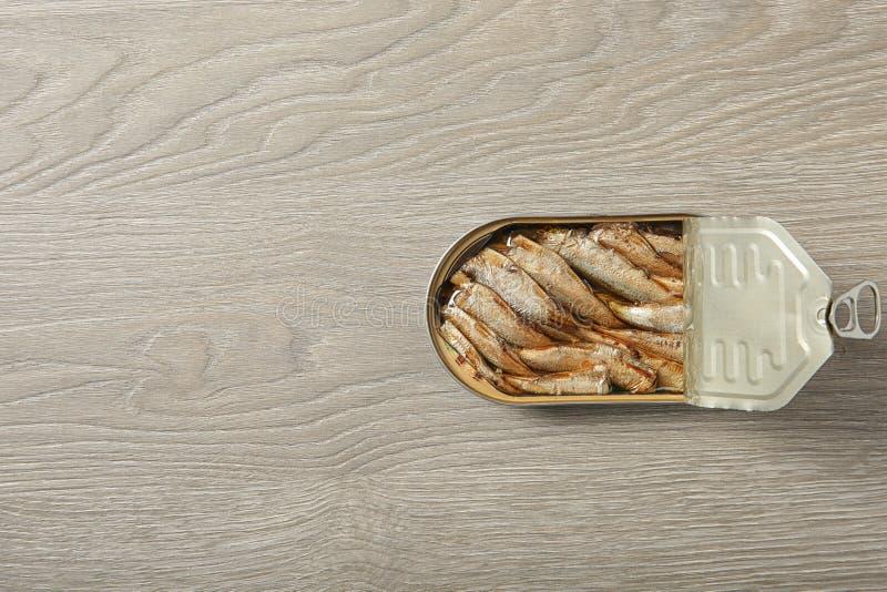 Barattolo di latta aperto degli spratti su fondo di legno, vista superiore fotografia stock libera da diritti