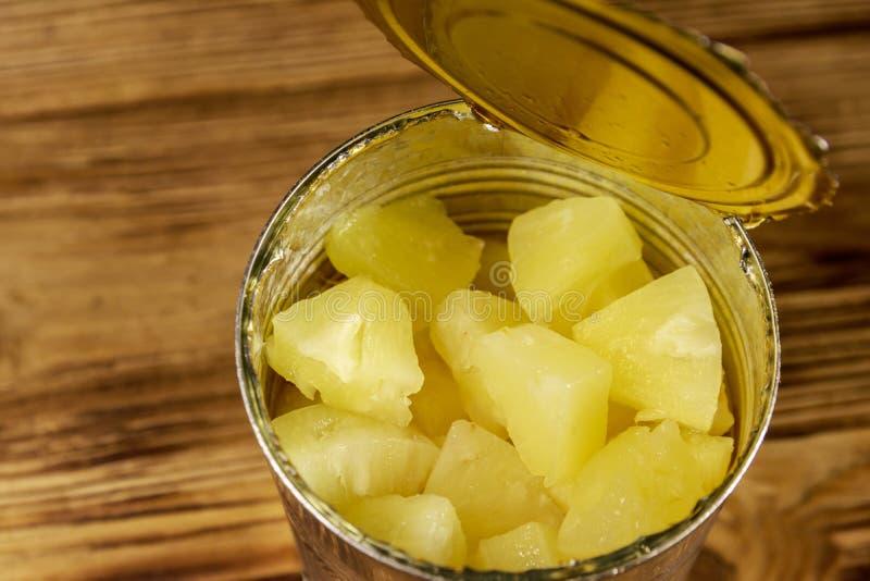 Barattolo di latta aperto dei pezzi dell'ananas sulla tavola di legno immagini stock libere da diritti