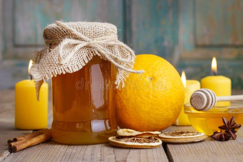 Barattolo di miele, delle arance e delle candele sulla tavola di legno fotografia stock