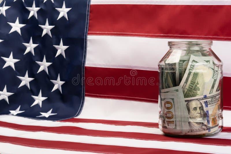 Barattolo di vetro con i dollari che stanno su una bandiera fotografia stock libera da diritti