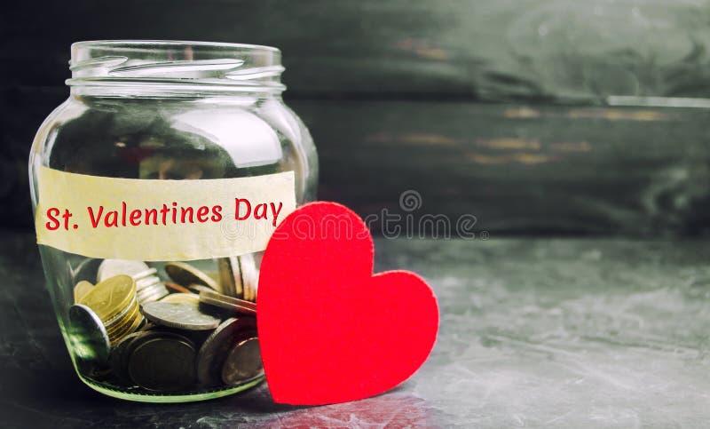 """Barattolo di vetro con il San Valentino dell'iscrizione e dei soldi """" """"L'accumulazione di soldi per la festa Risparmio sull'acqui immagine stock"""