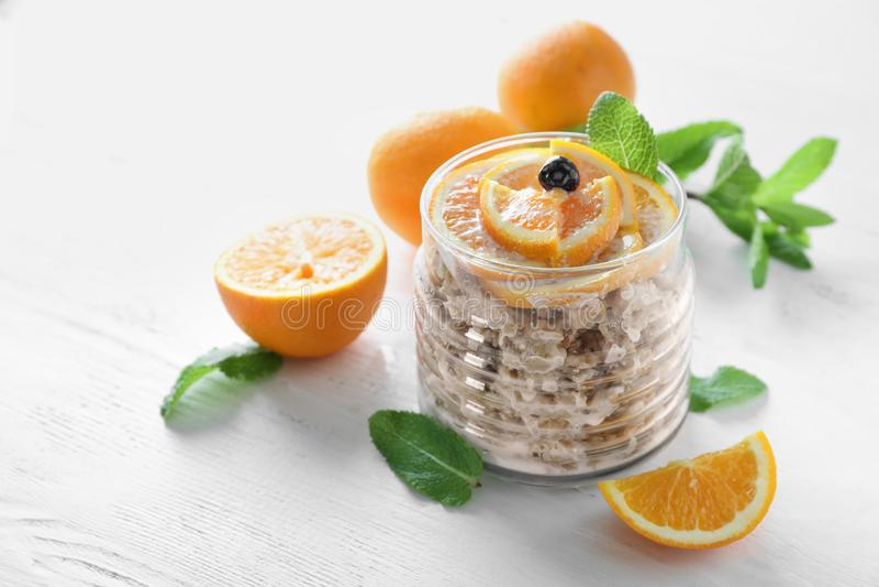 Barattolo di vetro con la farina d'avena saporita e l'arancia affettata su fondo leggero immagine stock libera da diritti