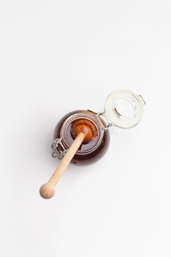 Barattolo di vetro con miele ed il cucchiaio di legno su un fondo bianco Vista superiore Copi lo spazio fotografia stock