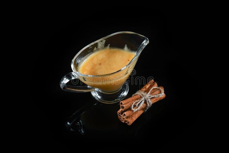 Barattolo di vetro in pieno dei bastoni di cannella e del miele legati su fondo nero fotografia stock libera da diritti