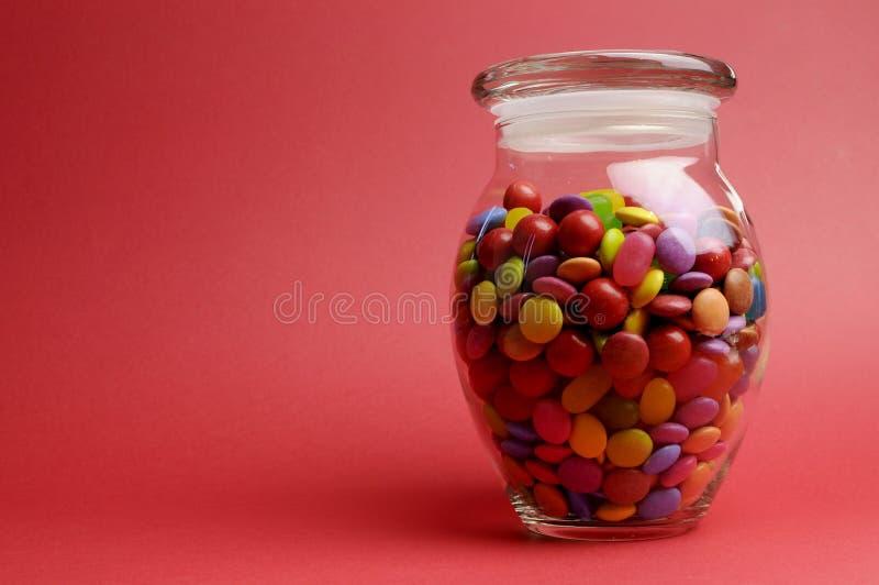 Barattolo di vetro in pieno dei lecca lecca e della caramella variopinti luminosi con il coperchio chiuso con lo spazio della copi fotografie stock libere da diritti