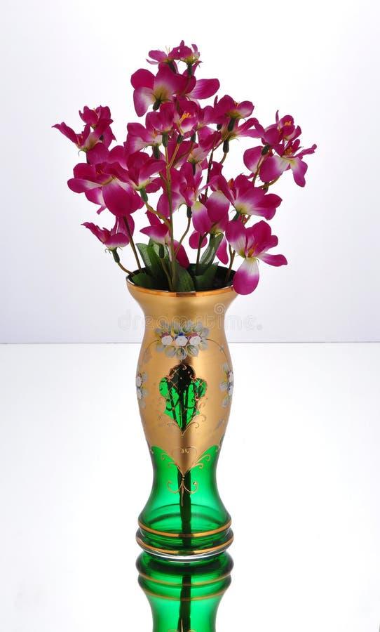 Barattolo di vetro verde con i fiori porpora fotografia stock