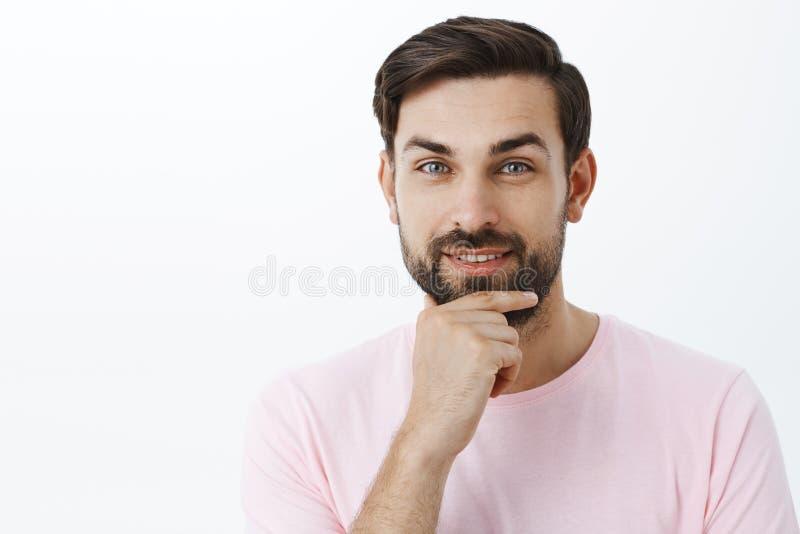 Barba hermosa ambiciosa y carismática contenta del frotamiento del hombre que sonríe con placer en la cámara que tiene idea inter fotos de archivo