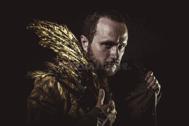 Barba modelo y traje del hombre hechos con las alas de oro imagenes de archivo