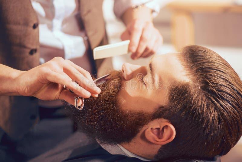 Barba professionale di taglio del barbiere dell'uomo bello immagine stock libera da diritti