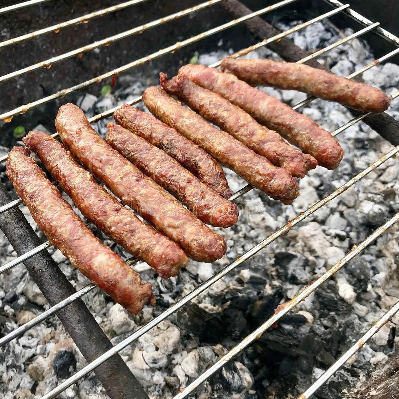 Barbacoa con las salchichas bávaras ardientes en parrilla en jardín al aire libre fotografía de archivo