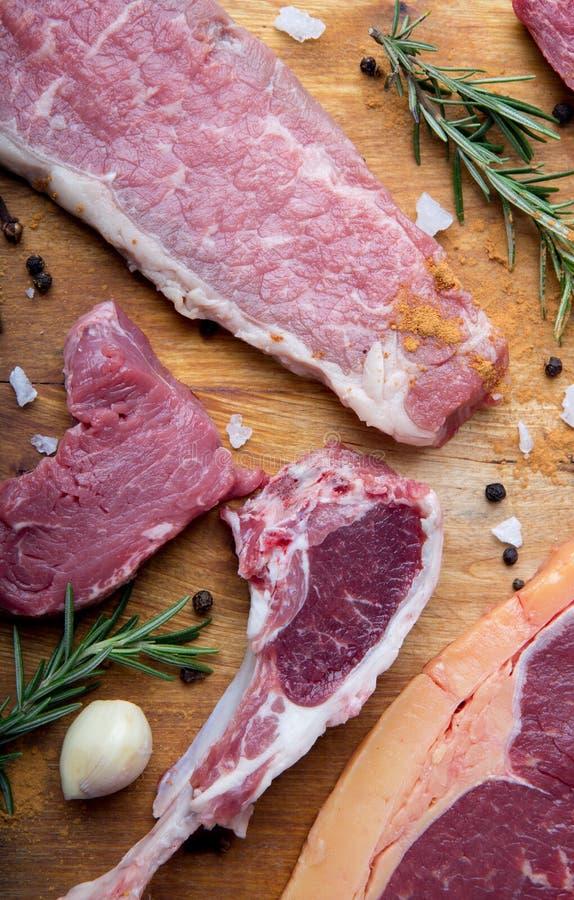 Barbacoa cruda de la carne de vaca con romero, ajo y pimienta foto de archivo