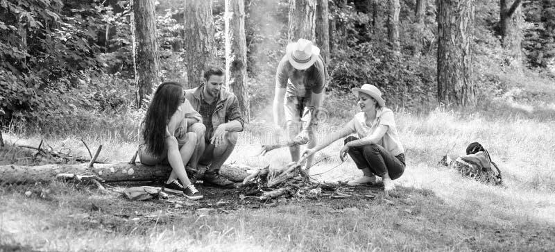 Barbacoa del alza Los amigos gozan de la barbacoa del fin de semana en compa??a del bosque que meriendan en el campo los amigos o imagen de archivo libre de regalías