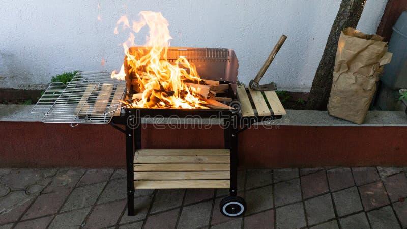 Barbacoa del jardín con el fuego que consigue la carne lista para guisar para un partido casero Llama en el Bbq Carbón de leña y  fotos de archivo