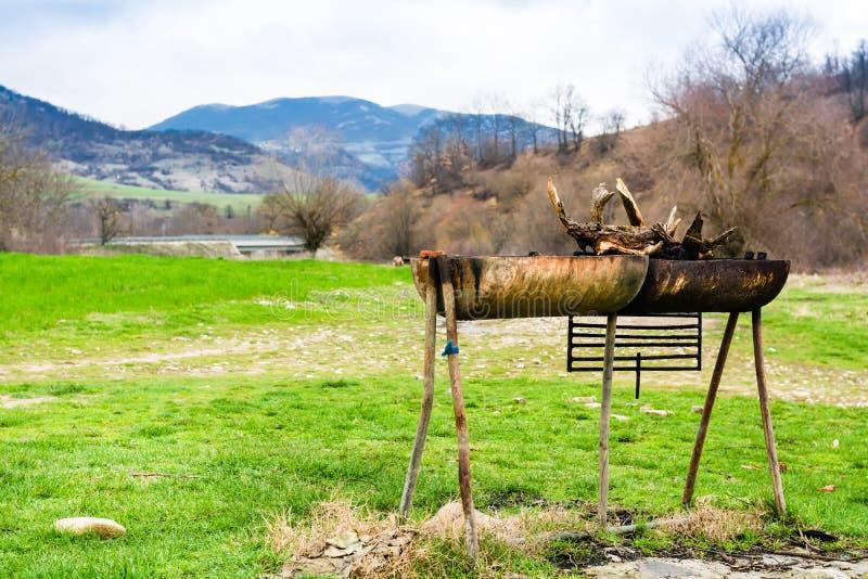 Barbacoa en el bosque Prado y montañas verdes imagenes de archivo