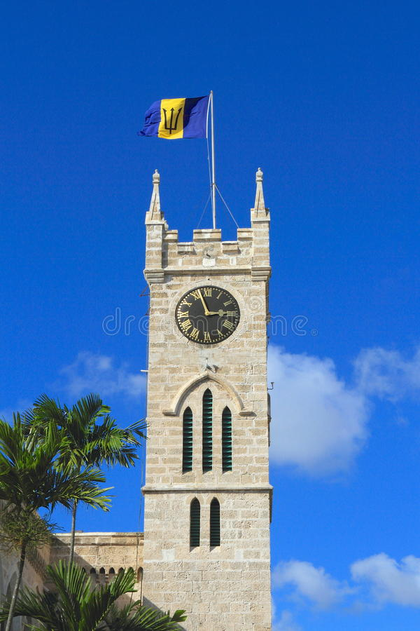 Barbados/Bridgetown: Parliament/Clock Tower with National Flag. The Parliament - built between 1970 and 1874 - consists of two neb-Gothic buildings. The tower stock image