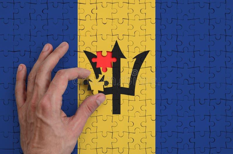 Barbados señalan por medio de una bandera se representan en un rompecabezas, que la mano del ` s del hombre termina para doblar imagenes de archivo