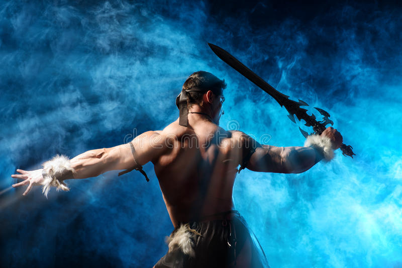 Barbarian. Portrait of a handsome muscular ancient warrior with a sword royalty free stock photos