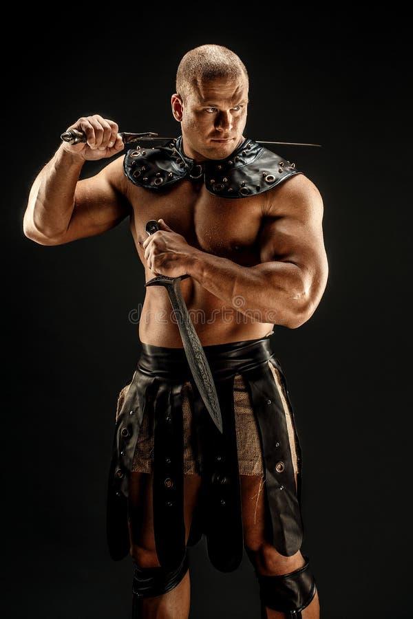 Barbaro severo in costume di cuoio con la spada immagini stock