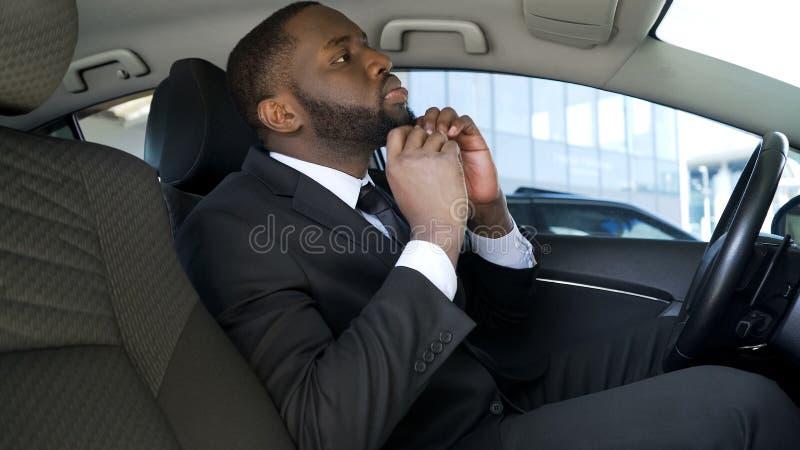 Barbe smartening d'homme d'affaires afro-américain, regardant dans le miroir de voiture rétroviseur photographie stock