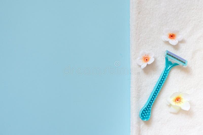 Barbeador azul da senhora com o trajeto de grampeamento na toalha branca no fundo azul com espa?o da c?pia Flores brancas Lugar p imagem de stock royalty free
