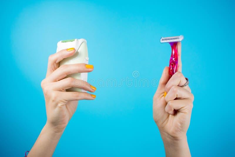 Barbeador e epilator vermelhos nas mãos da mulher fotografia de stock royalty free