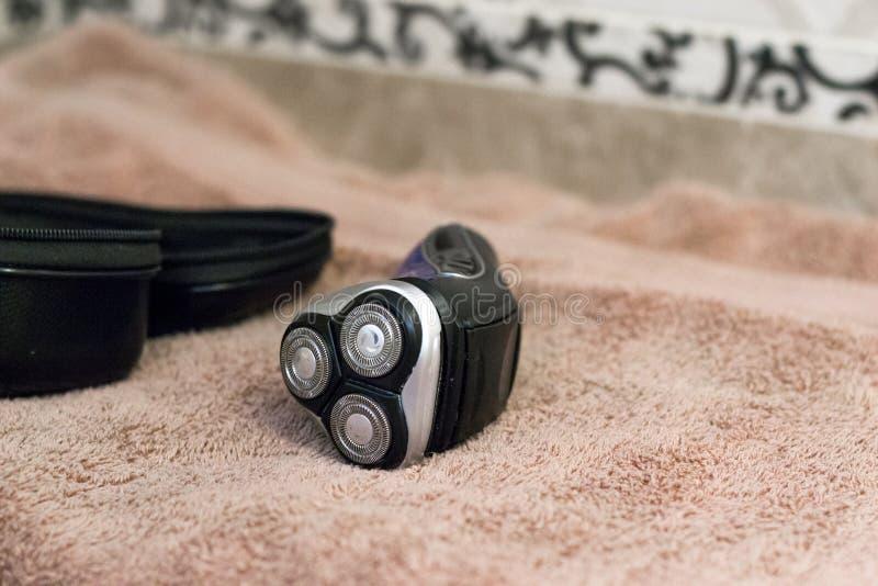 Barbeador giratório azul elétrico com as três lâminas perto das toalhas pretas do caso e de banho imagens de stock royalty free