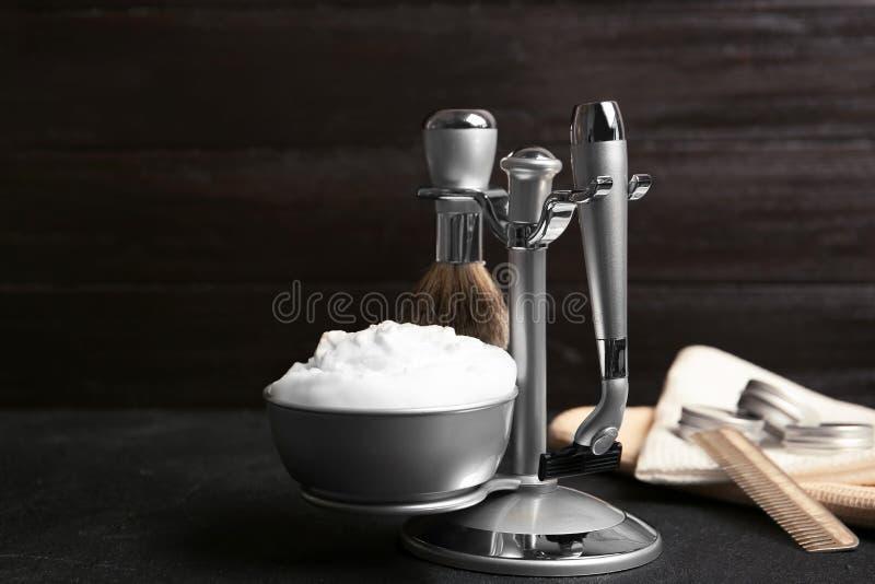 Barbeando acessórios na tabela contra o fundo escuro imagem de stock