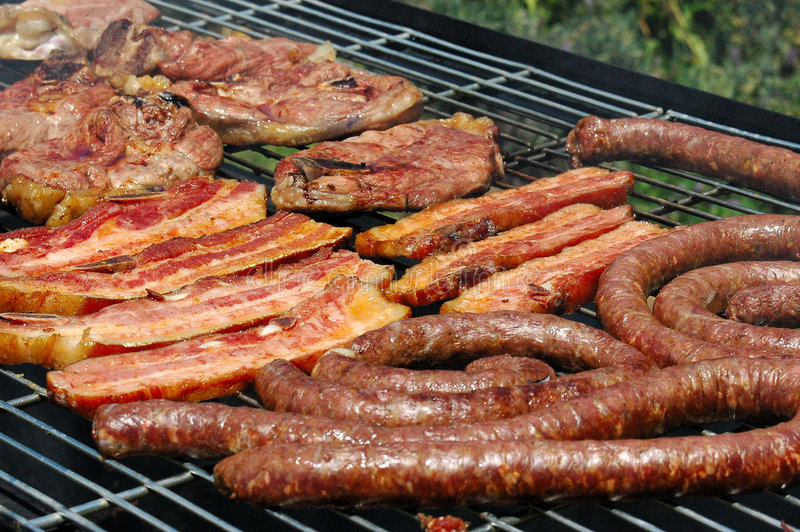 Barbecue. Grilled pork meat, lamb chops and sausages on a grill for a barbecue (traditional South African Braai) in summertime outdoors in South Africa royalty free stock images