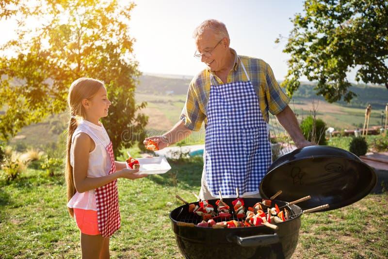 Barbecue in aard - glimlachende familie royalty-vrije stock afbeeldingen