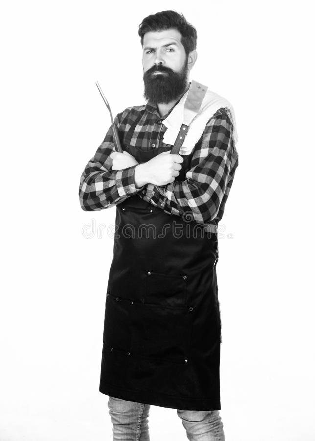 Barbecue accessories. Bearded man holding grill gripper tools. Hipster in apron with metal utensils for barbecue grill. Grill cook. Cooking barbecue. Preparing royalty free stock photography