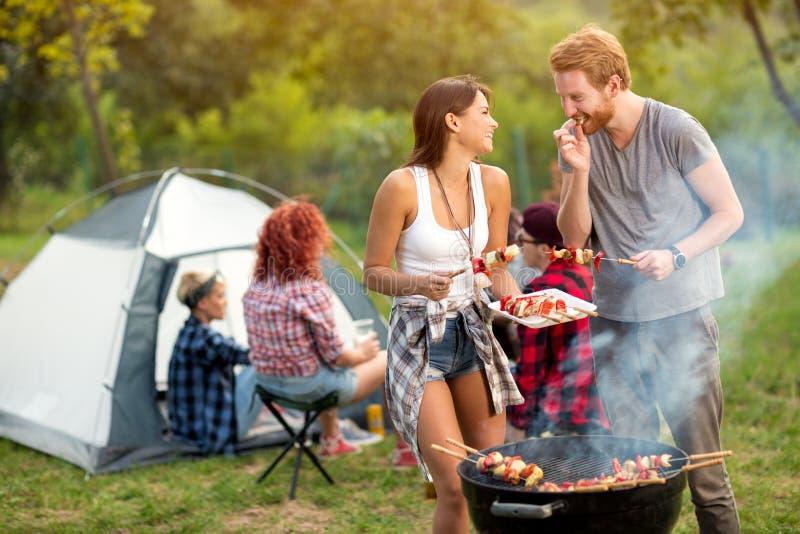 Barbecue arrostito assaggio dell'uomo e della giovane donna fotografia stock