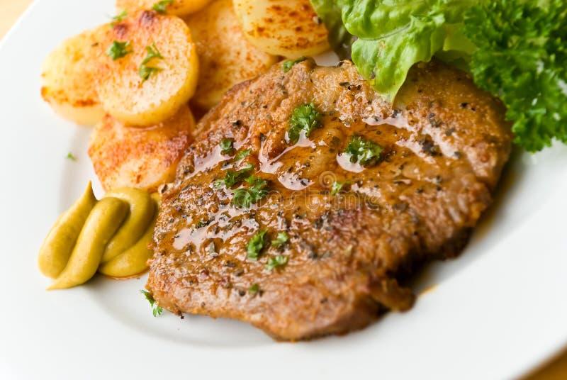 Barbecue avec des biftecks de porc, pommes de terre frites, salade images libres de droits