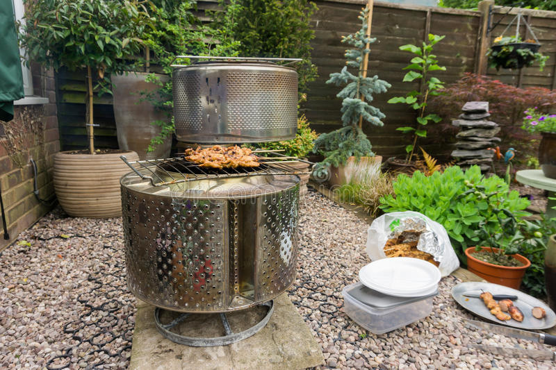 Barbecue in a back garden. Made from a washing machine drum stock photo