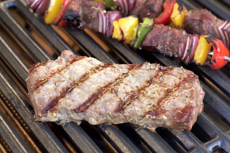 barbecue Bife grelhado, no espeto e pimentas grelhadas, cebola, na grade quente imagem de stock