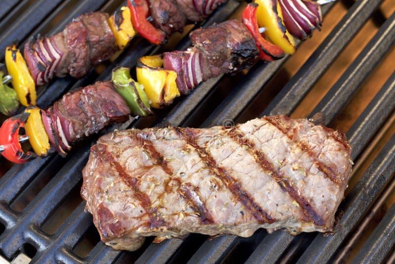 barbecue Bife grelhado, no espeto e pimentas grelhadas, cebola, na grade quente fotografia de stock