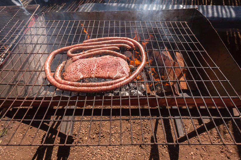 Barbecue Braai Meat Grill. Closeup of meat sausage and steak cooking on open fire barbecue braai grill at outdoor camping venue stock images