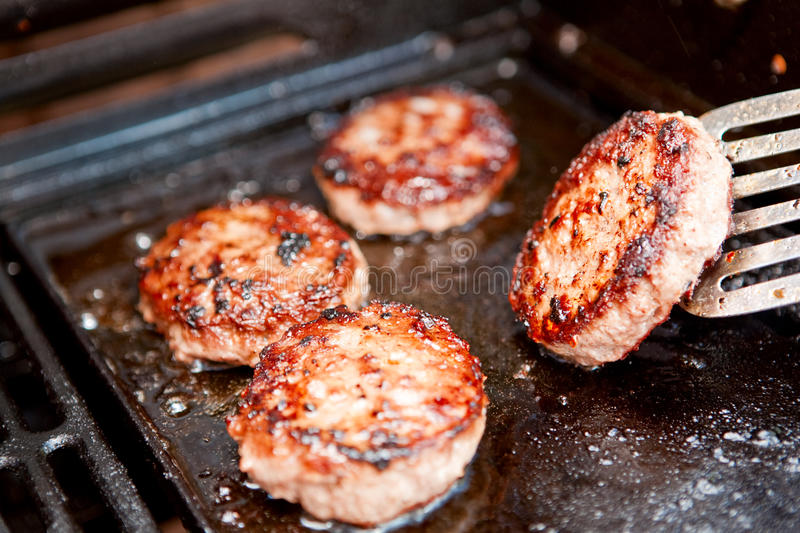 Barbecue burgers. Burgers cooking on a barbecue - selective focus royalty free stock photo