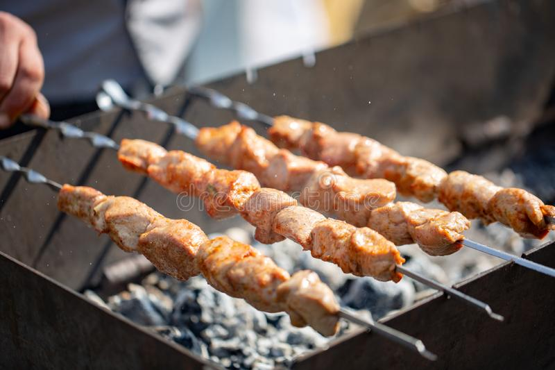 Barbecue Chiche-kebab juteux sur le gril Le chiche-kebab sur des brochettes frites sur les charbons chauds, fumée aromatique se l photo stock