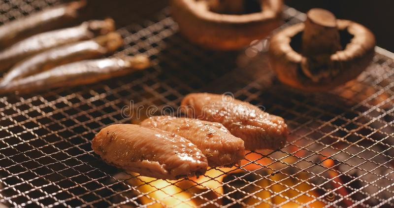 Barbecue with chicken wing, mushroom and capelin fish on grilled. Net at outdoor stock photos