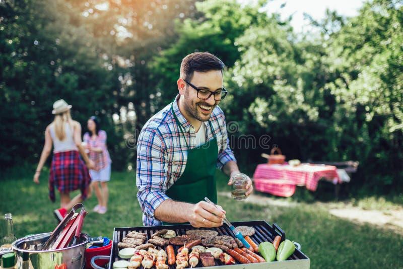 Barbecue de préparation masculin dehors pour des amis photo libre de droits
