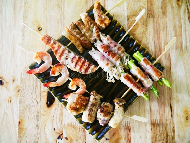 Barbecue de viande et de fruits de mer de poulet frit avec des légumes sur les brochettes en bois sur une sauce à plat Vue supéri photos libres de droits