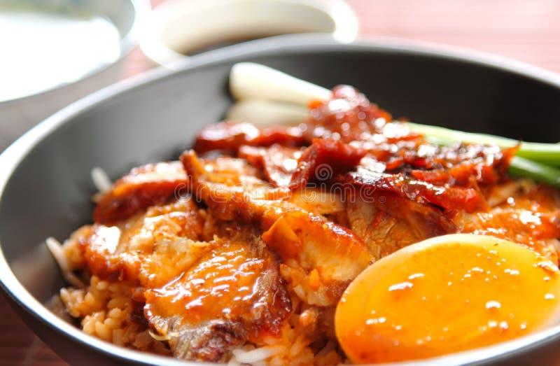 Barbecue en knapperig varkensvlees met jussaus op rijst royalty-vrije stock afbeelding