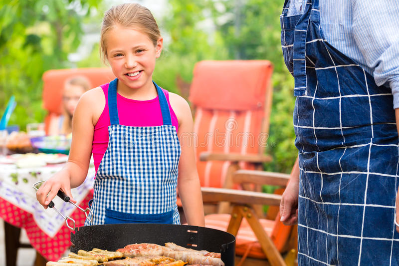 Barbecue with family in the garden. Father and daughter making barbecue in the garden in summer with sausages and meat stock photos
