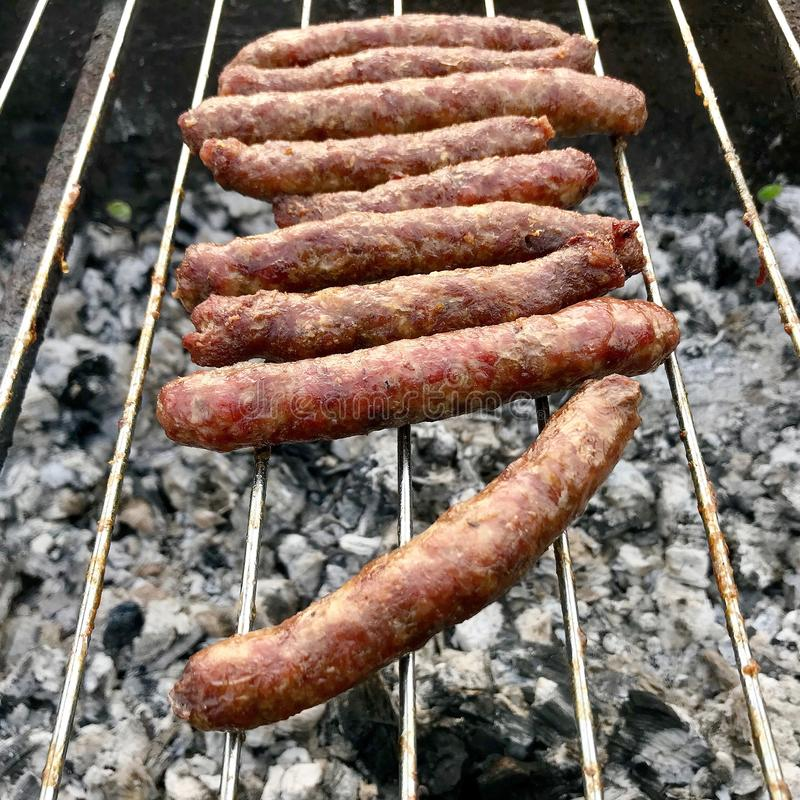 Barbecue with fiery Bavarian sausages on grill in garden outdoors royalty free stock photos