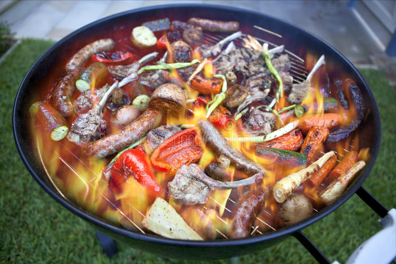 Barbecue Flame Fire Grill Food. A barbecue full of meat and vegetables on a barbecue grill with lots of flame and sizzling food stock photos
