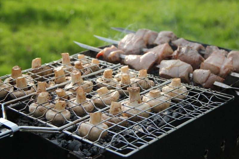 Barbecue: geroosterde paddestoelen en geroosterd vlees royalty-vrije stock afbeeldingen