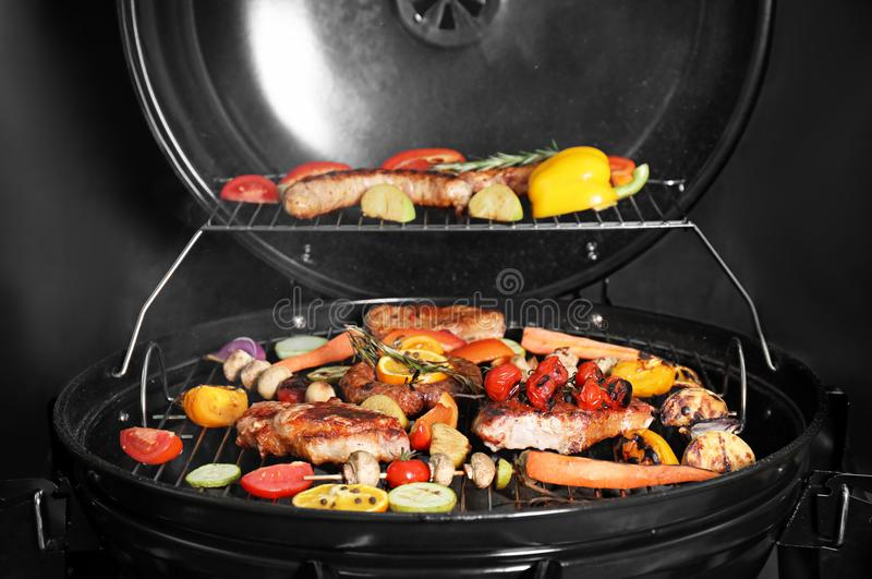 Barbecue grill with delicious cooked meat. And vegetables on black background royalty free stock image