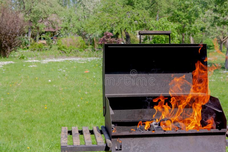 Barbecue grill with fire in the garden outdoor close up view.  royalty free stock photography